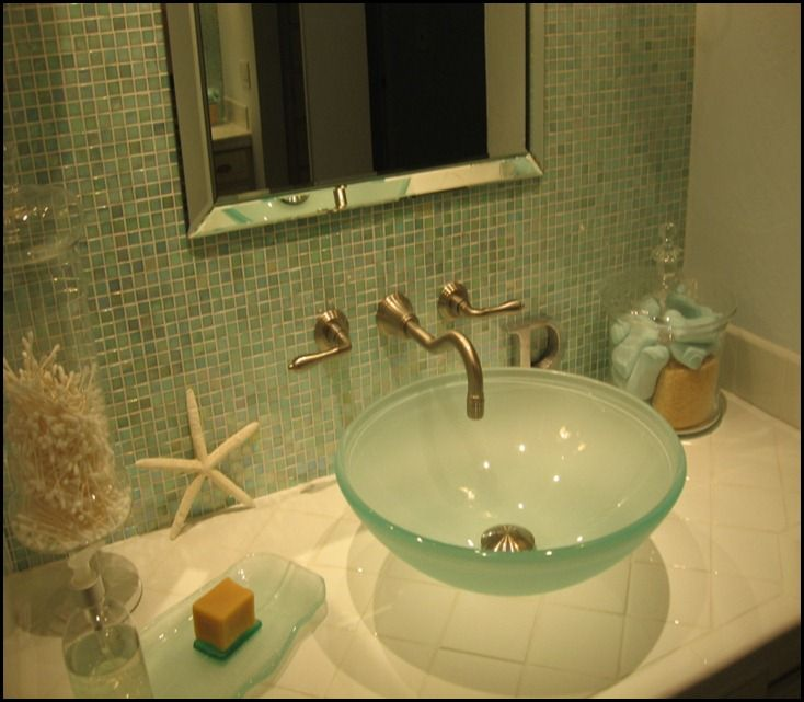 small but spa-like, bathroom done in ocean blues and greens, iridescent glass tile  wall behind vanity mirror all the way to the ceiling with a frameless mirror.