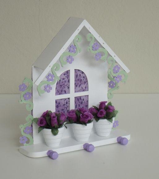 Porta chaves super charmoso e delicado para decorar sua casa e organizar suas chaves!    Casinha porta chaves em mdf com 3 pinos em madeira e flores vazadas nas laterais.  Na cor branca com detalhes nas cores verde e lilás.  Com cortina (tecido na parte de trás) na cor lilás.  Com 3 mini vasinhos em cerâmica branca com arranjos de mini rosas de tecido.  Envernizada.    Medidas: 21cm de altura x 18,5cm de comprimento R$ 67,00
