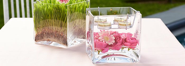 2 Clearly Creative™ Cube Tealight Holders, one filled with grass and the other shown with lit Tealights and flowers #wedding #centerpieces #partydecor