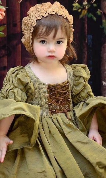 Precious little girl in a medieval gown and cap. (No further information available. :( )