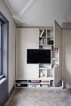 Pra quem gosta de um ambiente mais clean, mas precisa aproveitar ao máximo o espaço, essa é uma dica interessante. O painel da TV se abre e esconde um armário, onde é possível guardar muitas coisas.