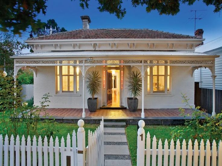 concrete victorian house exterior with picket fence and landscaped garden