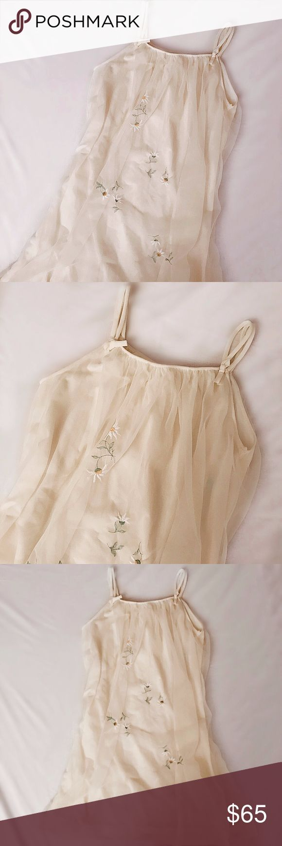 """1970s """"Pale Santon"""" Embroidery Slip Pale Santon yellow, gently tufted slip dress featuring delicate bow-detailed double straps and daisy embroidery throughout. From the 1970s, kept in brand new condition. Pair with some slides or an ankle boot. Fits like a size S-M, 33""""L and 18""""pit to pit. Retail value $120. -Olivia Cheng Curated Vintage- Vintage Dresses Mini"""
