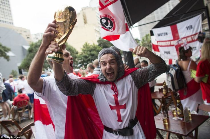 Hurrah! An England fan dressed as St George holds aloft a replica of the World Cup