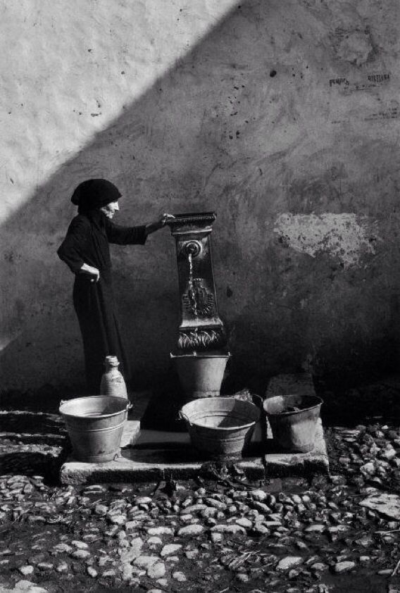 Sicily. Old lady collecting water. Timeless