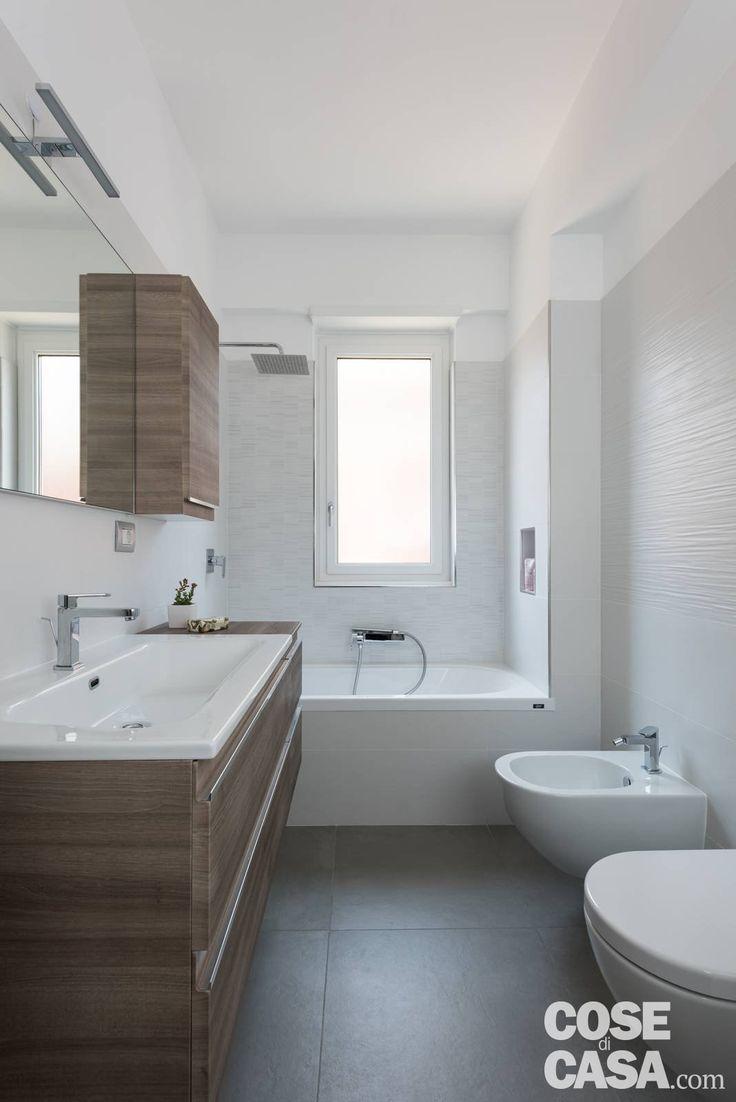 La parete attrezzata del soggiorno e il setto di vetro e ferro della cucina danno carattere a un appartamento romano di 45 mq total white.