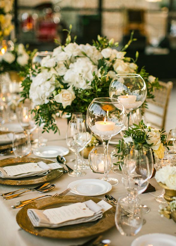 Elegant banquet tables ...♥♥... were covered with green and white floral arrangements in varying heights all accented by classic gold.