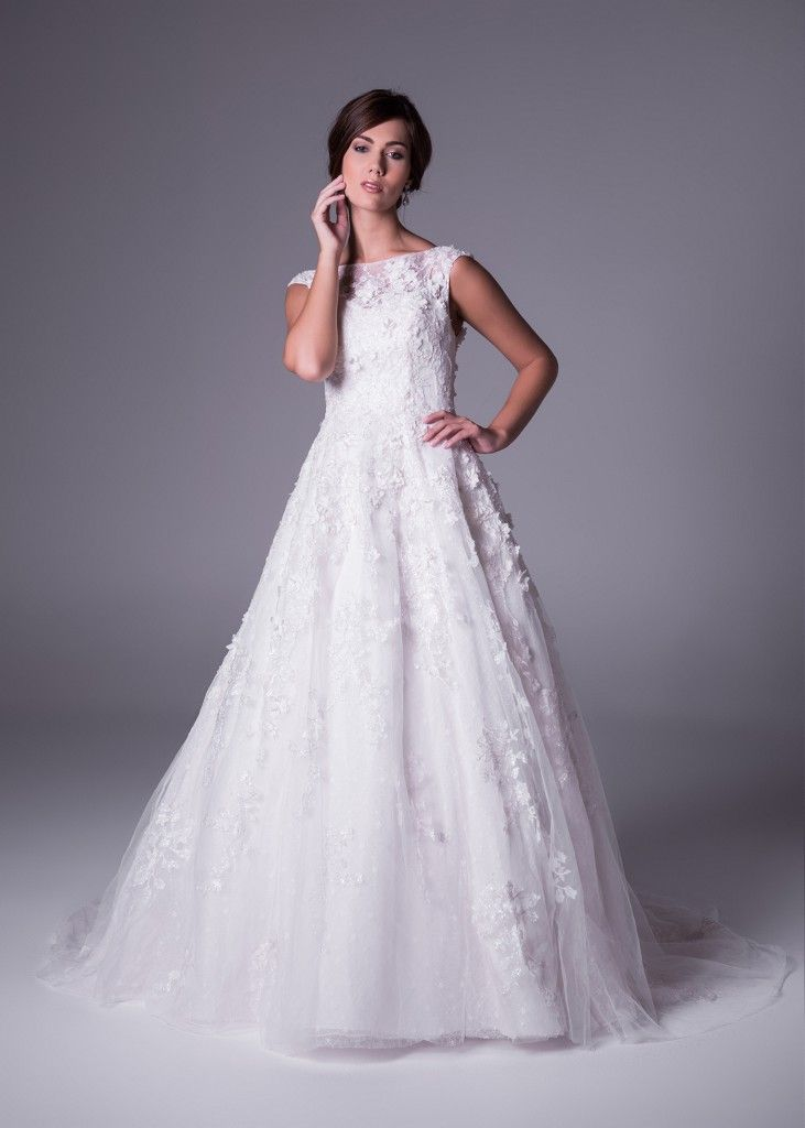 Available in Whisper Pink and traditional ivory! With a magical 3-dimensional flower design, this flattering A-line style dress has an elegant bateau neckline (style CWG659). Click to Book a Fitting.