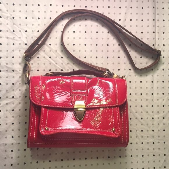 Single Handle Mini Ecole Satchel Handbag in Red This is London calling, are we reaching? Grab this British bag for a night out with the girls. Shiny patent red can't be missed, and the 3 interior compartments will store a small wallet, your phone, and several tubes of lipgloss. Stash your cash in the zippered pocket in the main interior space and head out. This bag includes a detachable strap as well as an attached satchel handle. From UK store Marks & Spencer. Marks & Spencer Bags Satchels
