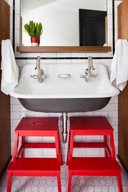 A kids bathroom, built for two. A trough sink and bright step stools make this space bright and cheery for littles.