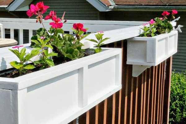 Hang planter boxes on the railings. You can DIY your own for a fraction of the cost of pre-made boxes.