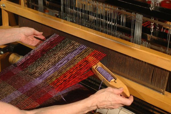 Weaving shuttle to insert weft picks.