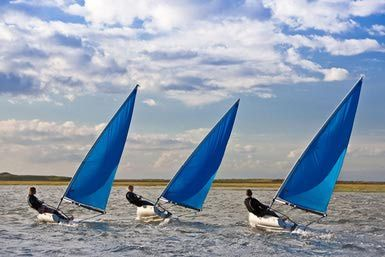 Two men and a woman race each other in small sailing dinghys in windy conditions. - Tim Platt/Iconica/Getty Images