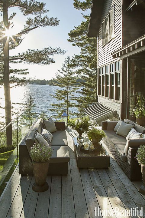 "GLASS BARRIER – On the deck outside a Canadian cottage, Anne Hepfer installed frameless glass panels instead of railings, both for safety and to shield from wind blowing off the lake. What's more: ""It's the best spot to watch sunsets, since glass doesn't obscure the view."" Click for more patio ideas."