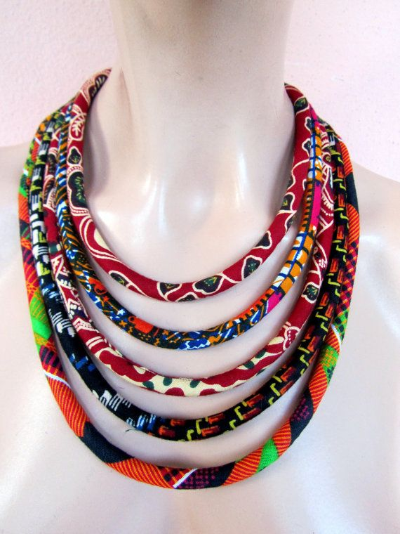 This is a special necklace that is made of african wax fabric cords. The cords are sewn and fitted around acrilic fiber. This awsome African inspired,trendy color necklace ,worn on dressy or casual clothes will definitely be noticed.  For matching earrings You can add a 19 mm or 0.7 inches diameter a fabric covered studd earrings in the fourth and fifth picture  Length from one end to the other in a straight line is 21.5 inches or 54.5 cm (inner circomference).I have also added 3 inches or 8…