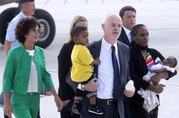 娘を抱いてイタリアの首都ローマ(Rome)の空港に降り立ったメリアム・ヤヒア・イブラヒム・イシャグ(Meriam Yahia Ibrahim Ishag)さん(手前右)とイシャグさんの息子を抱いているイタリアのラポ・ピステリ(Lapo Pistelli)外務副大臣(手前左)。マッテオ・レンツィ(Matteo Renzi)伊首相(奥右)とレンツィ首相夫人のアグネーゼ(Agnese)さん(左)がイシャグさん一家を出迎えた(2014年7月24日撮影)。(c)AFP ▼25Jul2014AFP|死刑取り消しのキリスト教女性、イタリアに到着 法王と面会 http://www.afpbb.com/articles/-/3021455
