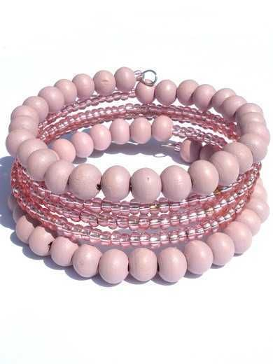 This bracelet is stringed on a spiral spring and is made with powder pink wooden and glass beads.