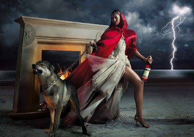 Eva poses as Little Red Riding Hood in a red hooded cape, beige gown with floral embroidery, and jeweled heels while holding a chain which is used to tame the scary wolf.    Read more: http://celebrity-event.com/eva-mendes-amazing-fairytale-photo-shoot-for-campari.html#ixzz1qjzu7YVW