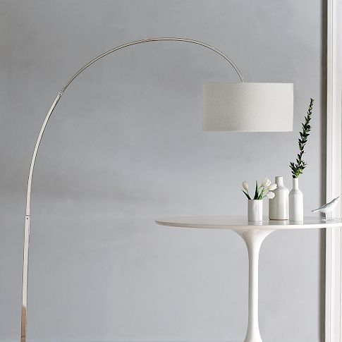 """A modern classic. Polished metal sweeps up in a graceful gravity-defying arc from the base of this Overarching Floor Lamp, finishing with a simple linen shade. The smart design allows overhead light to be cast anywhere in a room.    • Polished nickel base and arm; white linen shade.  • On/off foot switch.  • 19""""w x 61""""d x 77""""h."""