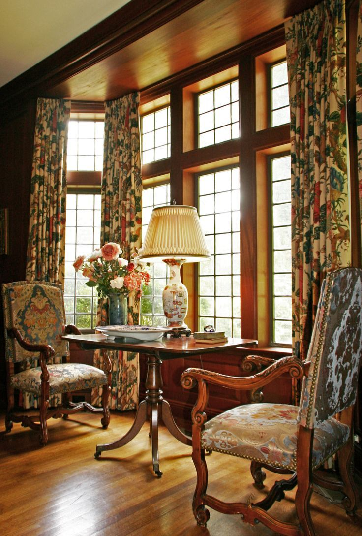 Lovely seating area in front of large window with stained wood ceiling; lovely antique table centered between two antique chairs upholstered in a beautiful fabric. Understated elegance!