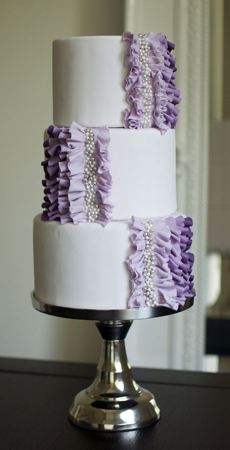 Wedding Cake With Purple Ruffles: Ombré is a popular wedding trend and we are loving this version by Sophie Bifield Cake Company, based in Canada. Pastry chef Sophie Bifield started with cake tiers covered in pale-lavender fondant, then fashioned gumpaste ruffles in varying shades of purple. The finishing touch? Pearls and silver dragées, each affixed by hand, to give the confection a touch of glitz and glamour.