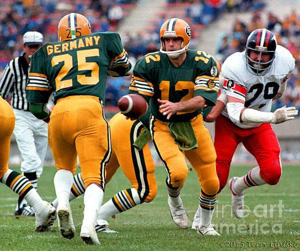 Photograph taken of Edmonton Eskimos QB Tom Wilkinson #12 handing the ball off to running back Jim Germany #25 in a 1981 game against the Ottawa Rough Riders.