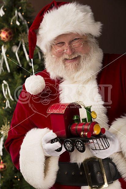 Santa Claus holding a toy train.