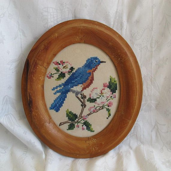 Charming cross stitched large bluebird in a striking rustic oval wood frame. Dimensions are 14 1/4 by 12 to the outside edge of the frame. Bird is about 6 1/2 inches tall. I just love the antique frame which looks to be hand made. Frame has glass. Nicely embroidered. Very good
