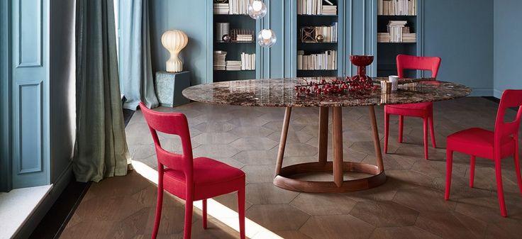 Il piano è realizzato in quattro tipi di marmo, in cristallo o ceramica, nelle due forme ovale e rotonda. La base è in legno massello disponibile in due diverse finiture: noce americano e frassino naturale o grigio.