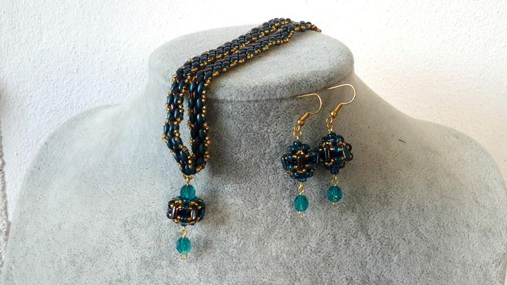 """Náhrdelník+""""Bonye""""+Šitý+náhrdelník+v+kombinaci+barev+modré,+zlaté+a+hnědofialové.+Šitá+donutka+je+zavěšená+na+šitém+pásku+z+korálků+superduo+a+rokajlu.+Zapíná+se+na+klasickou+kulatou+karabinku+ve+zlaté+barvě.+Obvod:+39+cm+++2,5+cm+prodlužovací+řetízek."""