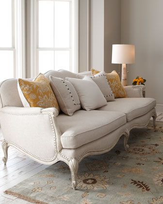 """""""Geneva"""" Sofa at Horchow.  A carved, exposed wood frame and nailhead trim lend casual elegance to this delightful sofa. Imported.  Solid hardwood frame.  Rayon/linen/polyester upholstery.  Textured, chipped-paint finish.  Comes with decorative pillows shown.  89""""W x 43.75""""D x 36.5""""T."""