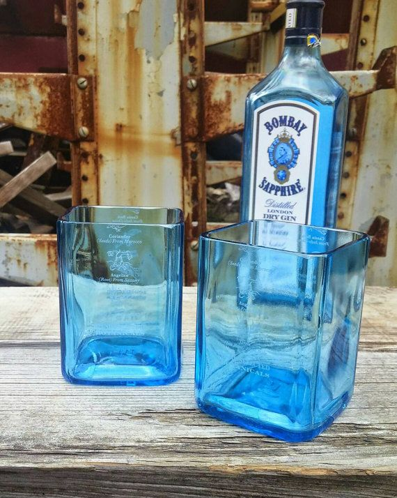 The Bombay Sapphire Blue liquor bottle is the pinnacle of elegance and makes amazing drinking glasses. These beautiful drinking glasses were created using recycled bottles which were cut, sanded, polished by both hand and machine to a spectacular finish and shine. WOW! your guests at your next gathering or surprise someone special with a unique handmade gift from recycled material. Each glass stands approximately 4.5 in height and holds up to 15oz Check out our shop for more great upcycled b…
