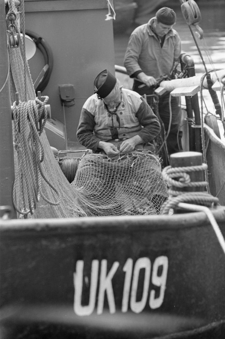 Urker vissers repareren netten aan boord. (Urk fishermen repairing nets on board.)