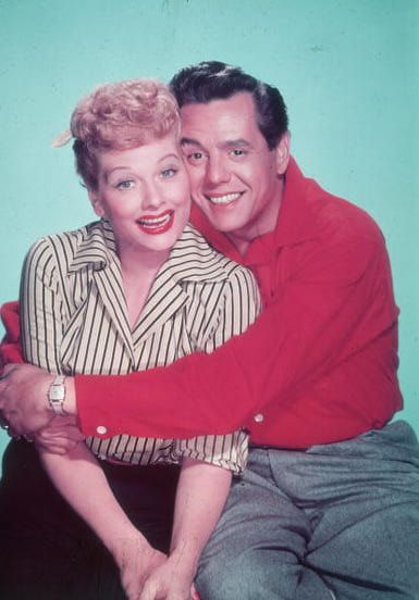 Studio portrait of American actor and comedian Lucille Ball receiving a hug from her husband, Cuban-born bandleader and singer Desi Arnaz, circa 1955.