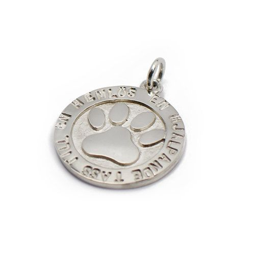 """Handmade silver pendant. This was the first LovePaws product ever made. It was created as a charity to support the rebuild of a burned down cat shelter in Sweden. In the middle there's a print of a cat paw and around it you can see the text """"En hjälpande tass för en hemlös"""" which means """"A helping paw for a homeless""""."""