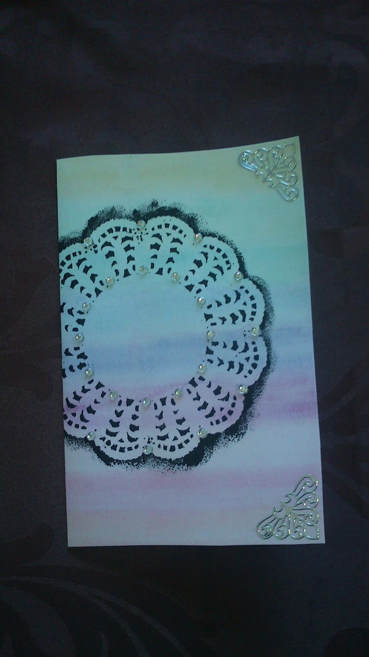Watercolored cardboard in rainbow colors. Then I put paper lace on it at painted thorugh it with black color, and then removed the paper lace. The corners are decorated with stickers.  -Louise Mirabilis