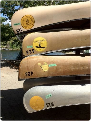 A fleet of aluminium canoes resting on the Portage Store dock in Algonquin Park.