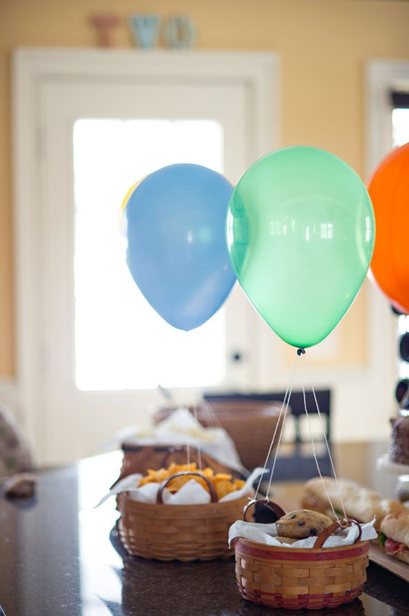Super easy way to decorate your travel themed party table - all food in baskets with a helium-filled balloon attached!