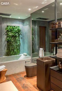 01-banheiro-e-tao-integrado-que-fica-quase-dentro-do-quarto Nada de compartimentos. Projetar uma sala de banho de 10 m² integrada ao quarto de casal. Como divisórias, apenas placas de vidro e persianas de madeira, usadas para garantir privacidade. Com réguas de 15 cm de largura, o piso de cumaru maciço promove unidade entre os ambientes e conversa com o marrom fosco das louças.