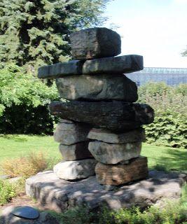 """Ce monument se trouve place de l'Assemblée nationale. Il a été dévoilé le 24 octobre 2002.  Sur la plaque de bronze près de monument on lit en langue inuit et en français:  """"Ce monument a été érigé en signe d'amitié entre le Québec et les Inuits. L'inukshuk évoque une forme humaine et sert de repère pour les habitants du grand nord québécois. Celui-ci a été réalisé avec des pierres provenant des quatre coins du Nunavik.*"""