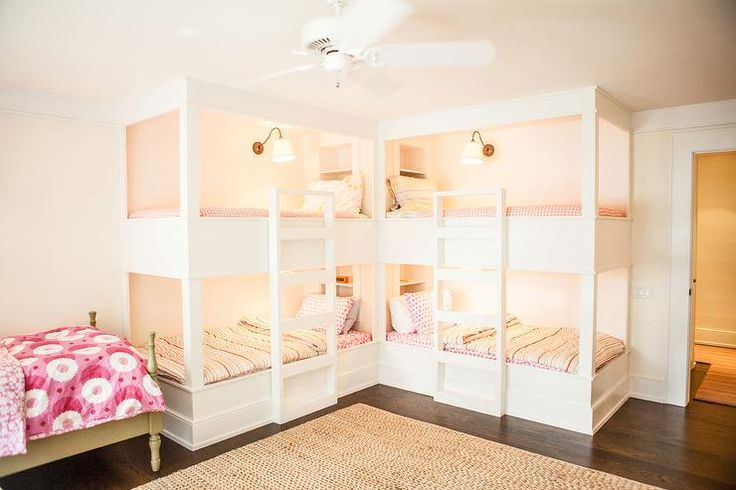 Sweet girls' bunk room features two pairs of bunk beds in L formation fitted with white ladders and dressed in pink polka dot bedding and pink stripe duvet covers illuminated by brass sconces with white plated shades.