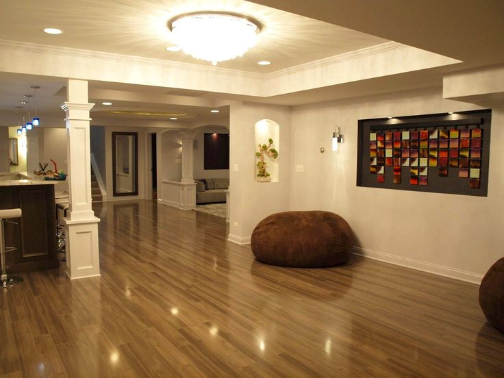 Appealing Basement Remodeling With Sleek Brown Laminate Wood Flooring And  Wood Bar And White Pillar Also