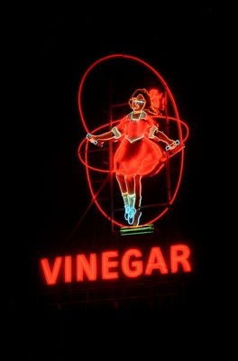Skipping Girl (aka Little Audrey) was one of the first animated neon signs in Australia, installed at Nycander & Co. Vinegar in Abbotsford, Melbourne, in 1936. There are three theories for Skipping Girl's true identity: a girl sketched in a children's competition (Kitty Minogue) another who used to skip near the factory (Alma Burns), and a junior artist at Claude Neone (Irene Barron). The sign is now solar powered and the logo still appears on Cornwell's vinegar products. Photo by Matt…