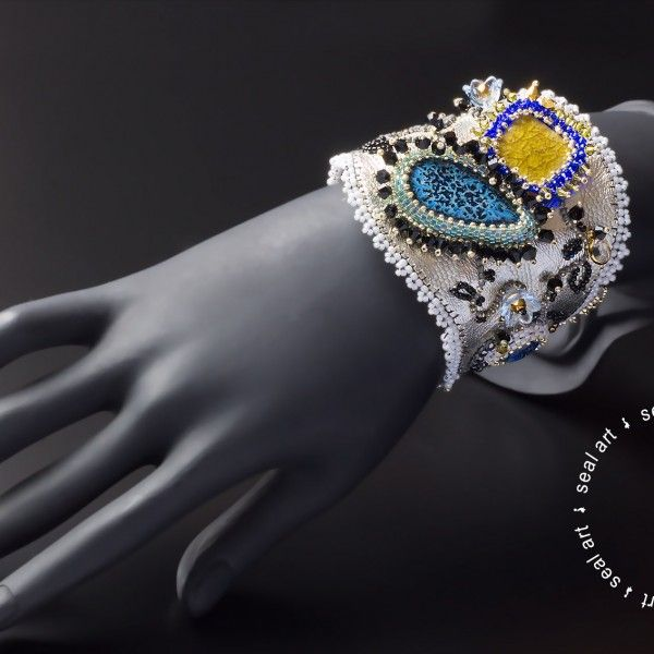 Piękna, elegancka, srebrzysta i skrząca. Bransoleta wykonana w całości na skórze naturalnej w trzech kolorach. Ozdobiona kaboszonami ceramicznymi, syntetycznym opalem. Wyszyta łańcuszkiem jubilerskim, koralikami Toho, Delica, oraz kryształami Swarovski. Zapinana na guzik i pętlę. Idealny prezent dla wyjątkowej kobiety!