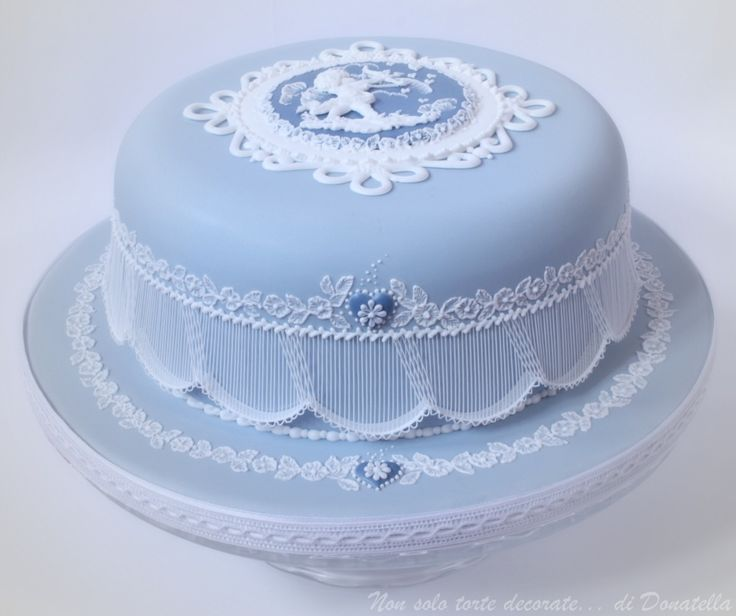 Inspired by Wedgwood and Eddie Spence. Royal Icing runout collar topper and pressure piping Cupid on the run-out blue plaque, brush emboidery on the sides of the cake and on the board with a little  royal icing run-out heart with a pressure piped daisy   Extension works on the sides of the cake. TFL