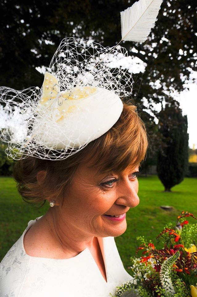 Bridal headpiece covered in lace, embellished with netting, an ivory arrow feather and butterfly