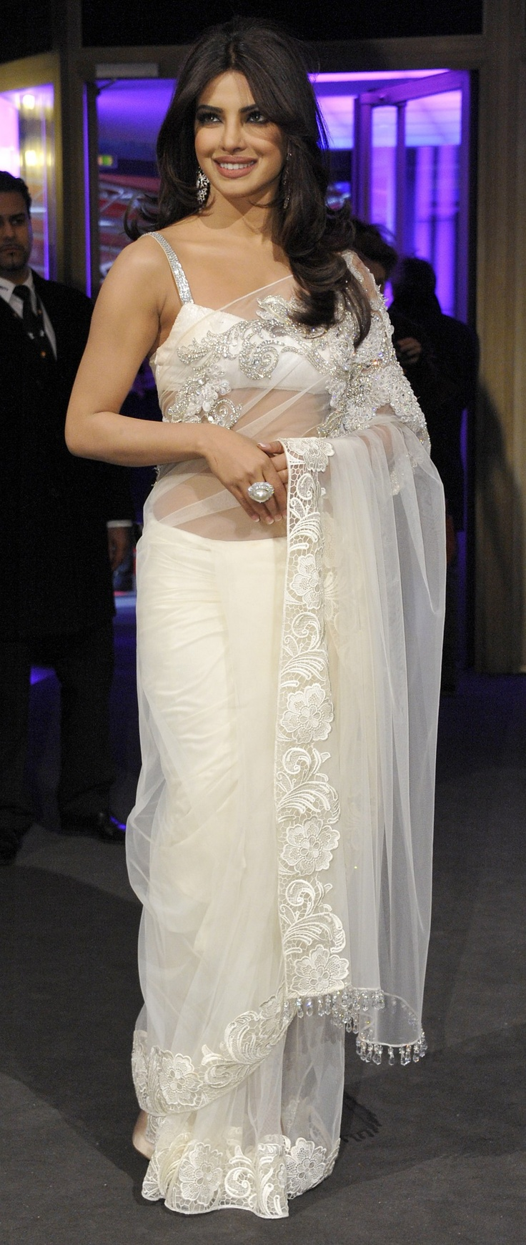 priyanka chopra sari is always as dashing and sensational as she herself is. In the above picture, the sari worn by Priyanka is embellished with beautiful embroidery, the border is done in velvet material. The blouse of the saree is also matching silk material as the saree itself. The blouse has been made as shorter as it could have been. There is a beautiful silver embroidery on the straps of the sari. The elegant net saree dazzles its way through evening parties especially receptions and