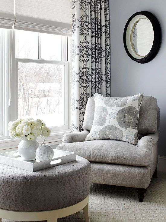 The Benefits of Texture: A tone-on-tone gray color scheme looks anything but dull in this bedroom seating area, thanks to a variety of textures. The chair features a rough linen upholstery, while the ottoman is covered with a nubby elevated pattern. The black-and-white draperies add subtle contrast without weighing down the light and airy space.