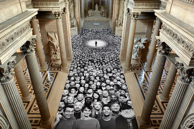Art installation covers monument in black and white portraits