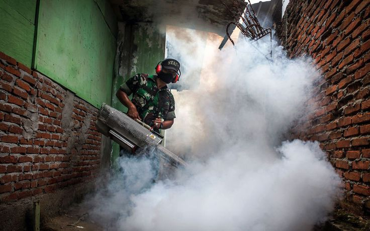 Army personnel and health ministry worker sprays anti-mosquito fog in Lhokseumawe, Aceh Province, Indonesia